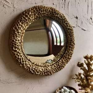 gold faux coral round mirror lifestyle against a pink wall
