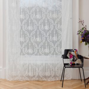 Ayrshire Lace Madras Window Panel - Chandelier Design.  Lifestyle image of panel hanging in front of a traditional window.
