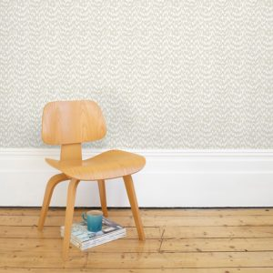 Florence Broadhurst Waterjet Wallpaper in Warm Grey on wall with chair in foreground at Curious Egg