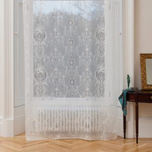 Ayrshire Lace Window Panel - Lydia Design.  Lifestyle image of panel hanging in front of a traditional window.
