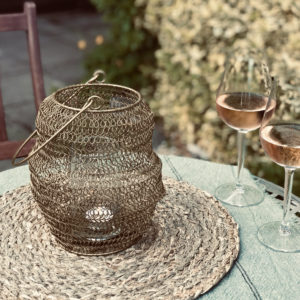 Gold wire garden lantern on outdoor table with wine glasses