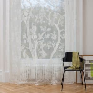 Ayrshire Lace Madras Windo Panel in Paradiso Design in Ivory colour. Lifestyle image of the Paradiso panel hanging in a traditional window.