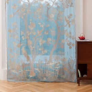 Ayrshire lace madras window panel - Paradiso in Turquoise colour. Lifestyle image of the panel hanging in a traditional window.