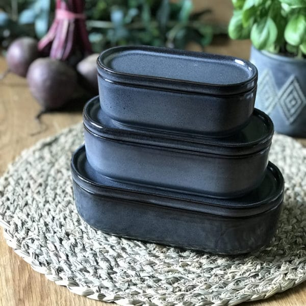 Slate blue food storage pots with grass matt and vegetables in background