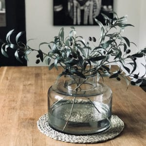 large recycled glass jar vase with olive branches displayed on wooden table