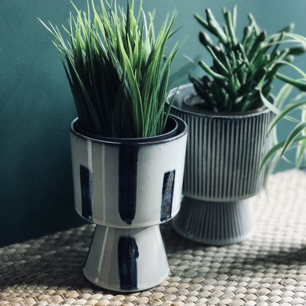 Stone coloured planter with dark blue tapies style brushstrokes on surface against green wall lifestyle image