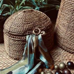 Curious Egg Belize Small Dome Lidded basket - lifestyle image of the basket with green foliage in the background.