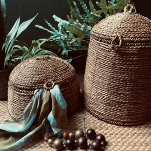 Curious Egg Belize Tall Dome Lidded basket - lifestyle image of the basket with green foliage in the background.