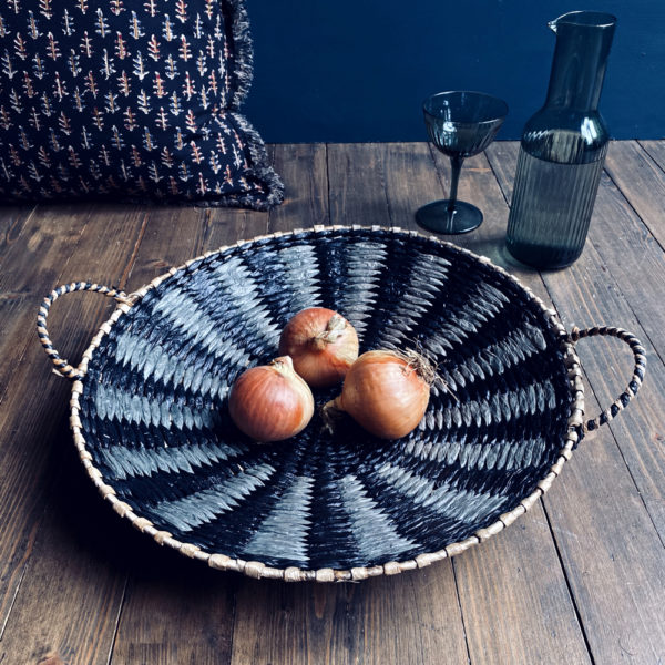 blue and black striped raffia basket with handles with onions in it and a blue background