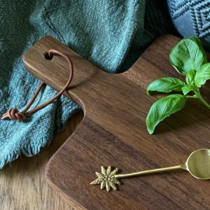 Curious Egg Walnut Wedge Chopping Board - lifestyle image of the chopping board with some basil leaves and a gold spoon.