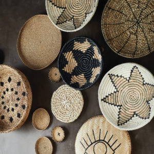 natural woven bowl grass with star motif on wall with other decorative woven bowls