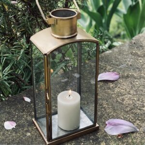 Brass finish lantern in garden with candle