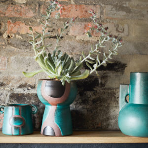 turquoise sculptural vase with our sculptural vases and plants on shelf