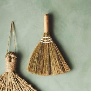 straw table broom hanging against sage green wall